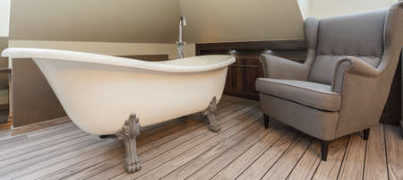vessel sink: Bathroom with elegant bathtube and cosy armchair
