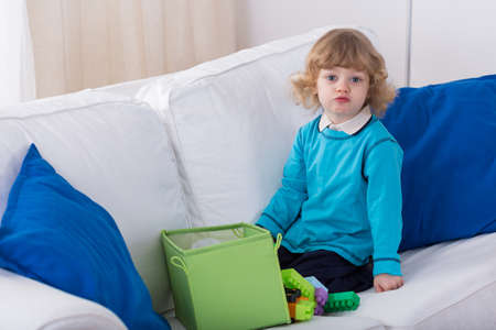 kindergartner: Cute blonde preschooler playing on the sofa