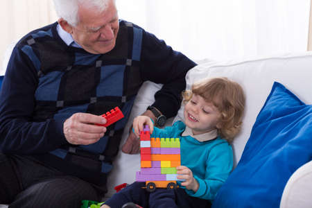 kindergartner: Grandpa and grandchild playing with colorful blocks Stock Photo
