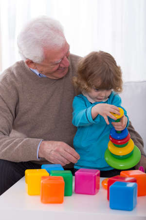 play blocks: Smiling grandpa and grandchild building color tower