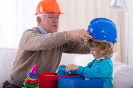 grandkid: Grandfather and grandkid wearing helmets during play