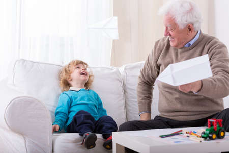 kindergartner: Smiling toddler and grandfather playing with paper plane Stock Photo