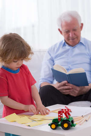 childchood: Good little boy playing alone in grandfathers house