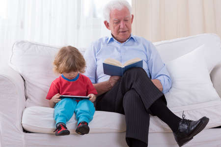 curly hair child: Grandfather and grandchild sitting on the sofa