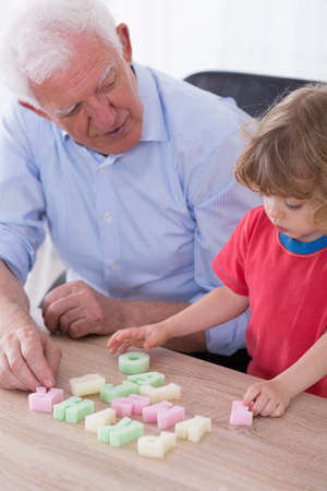 kindergartner: Image of loving grandfather teaching preschooler alphabet Stock Photo