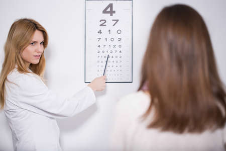 oculist: Young experienced female oculist examining the patient Stock Photo