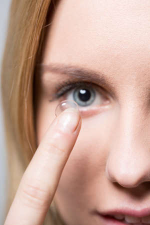 hyperopia: Close-up of young pretty woman putting on contact lens Stock Photo