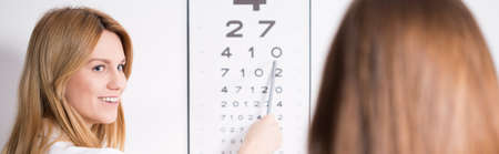 ophthalmic: Young pretty female ophthalmic optician and snellen chart Stock Photo