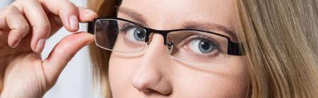 oculista: Primer plano de los ojos azules de la mujer joven detrás de unas gafas