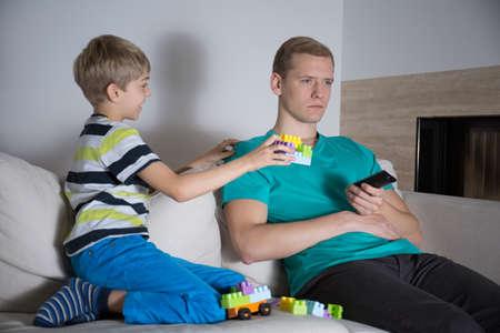 poner atencion: Padre joven que no prestan atención a su hijo