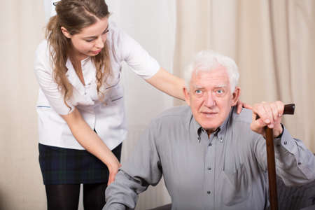 old and young: Careful female caregiver helping older man to stand up