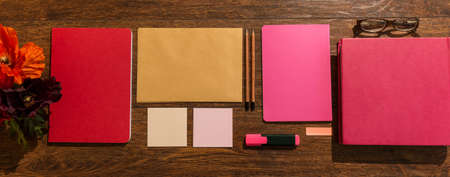 desk tidy: Pink and red notebooks prepared on wooden desk