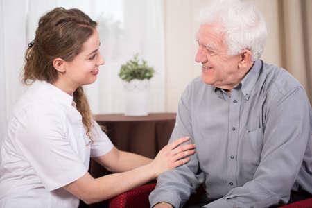 高齢男性の年金受給者および彼の非常に若い介護者の笑顔