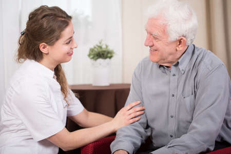 dos personas platicando: Sonriente jubilado Senior masculino y su bastante joven cuidador