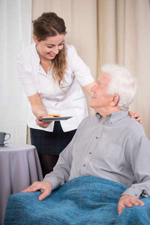caring nurse: Young caring nurse giving the dessert to older nice man Stock Photo