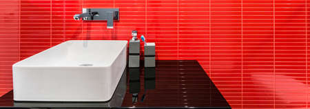 Elegant bathroom with white sink and red tiles, panorama photo