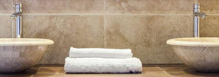 toallas: Blanco toallas dobladas limpias en el estante de mármol en el baño Foto de archivo