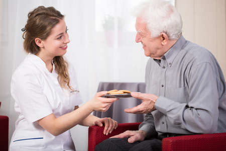 Pretty smiling female guardian serving cookies to older man photo