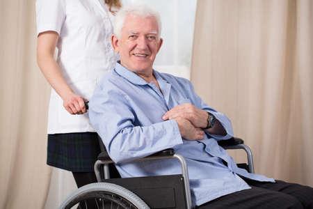 Senior injured smiling man sitting on wheelchair photo