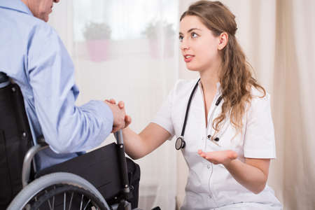 color therapist: Young pretty female doctor talking with her injured male patient