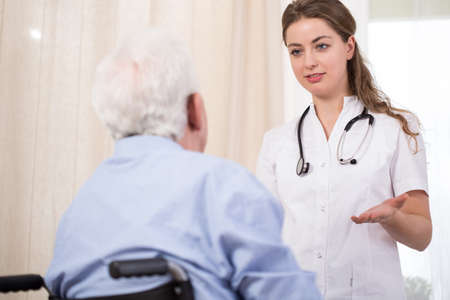 Conversation between young attractive nurse and older male patient photo