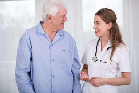 in pajama: Senior sick man in pajama and pretty smiling nurse Stock Photo