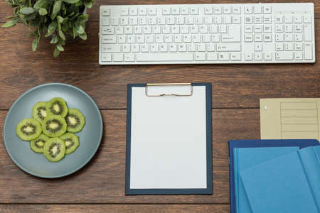 desk tidy: Tidy wooden office desk with plate of fresh kiwi Stock Photo