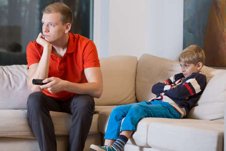 Bored child and father is watching TV at home photo