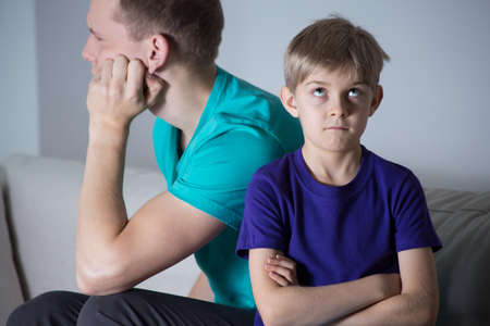 Immature young father and bored child sitting on couch photo