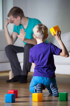 Depressed father ignores his son at home photo