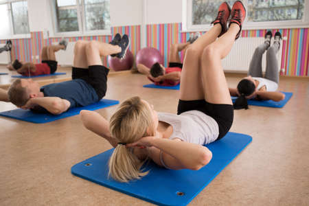workout: Group of people doing crunches on exercise floor mat Stock Photo