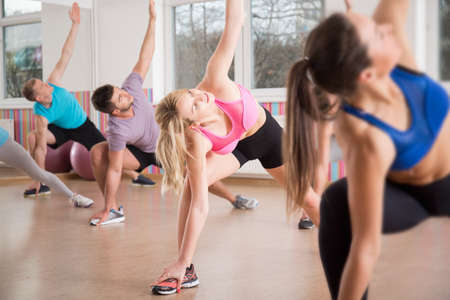 group cooperation: Fitness group stretching body during fitness classes