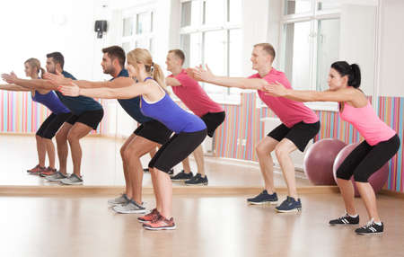 strengthen: Fit people doing squats to strengthen legs Stock Photo