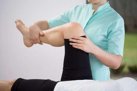 dislocation: Primer plano de fisioterapeuta haciendo ejercicio de miembro inferior Foto de archivo