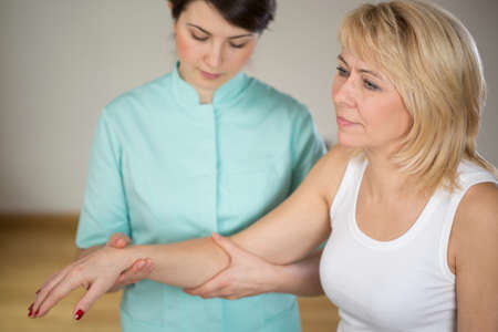 neurological: Adult woman during rehabilitation in physiotherapists office Stock Photo