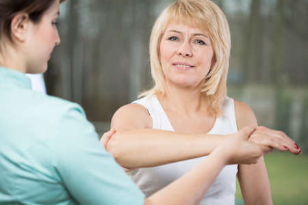 diagnosing: Young female physical therapist diagnosing painful arm