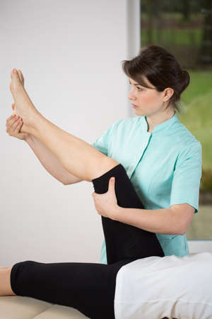 orthopaedist: Exercisie of lower limb on treatment couch Stock Photo