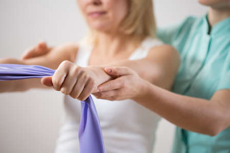 physiotherapist: Woman training with exercise band assisted by physiotherapist Stock Photo
