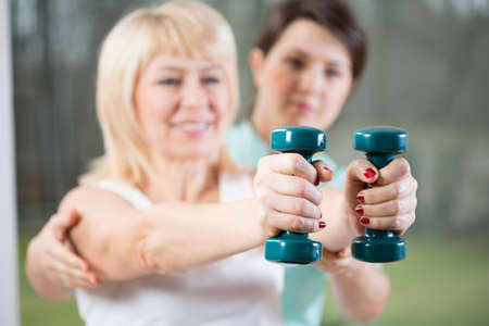 resistive: Female training with dumbbells assisted by physiotherapist