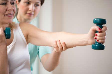 osteoporosis: Mujer que ejercita con pesas asegurado por fisioterapeuta