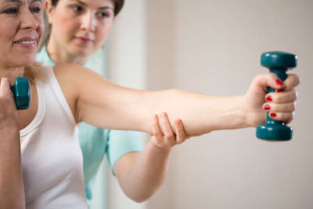 Woman exercising with dumbbells insured by physiotherapist