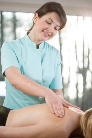beautician: Young female masseur massaging painful back of patient