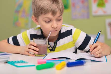 School child doing homework and drinking cacao Foto de archivo