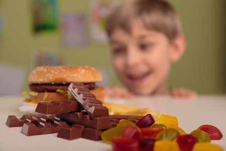 彼の不健全な給食を楽しんで笑顔の少年 写真素材