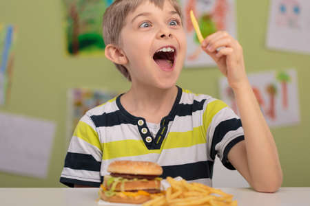 kids class: Happy boy eating french fries in school