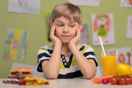 niños sanos: Muchacho que se desee - saludable o comida poco saludable Foto de archivo