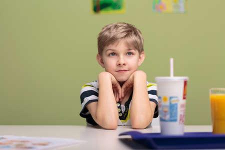 break in: Little boy having lunch break in classroom