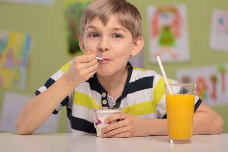 ni�os estudiando: Muchacho feliz que come el almuerzo saludable en la escuela