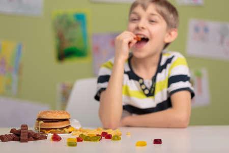 Sonriente que come niños ositos de goma en la escuela Foto de archivo
