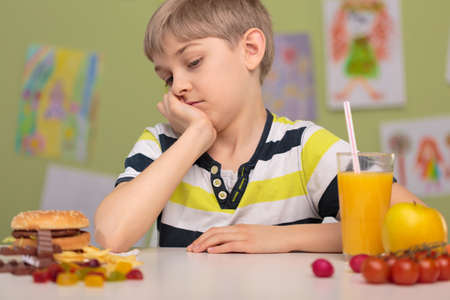 obesity kids: Healthy and unhealthy lunch on school desk
